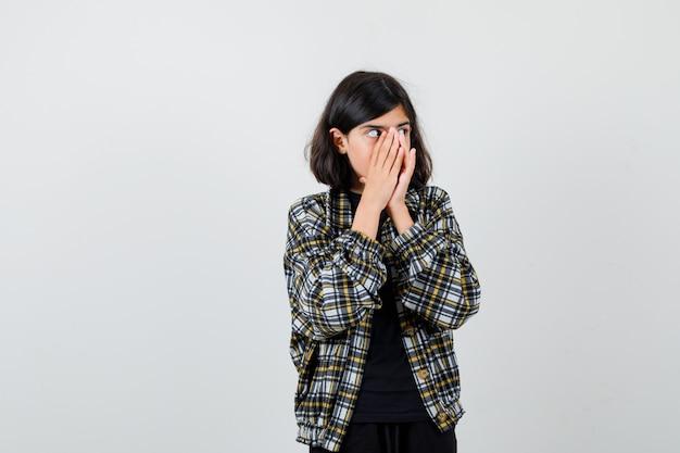 Teen dziewczyna trzymając się za ręce na twarzy, patrząc na bok w casualowej koszuli i patrząc w szoku, widok z przodu.