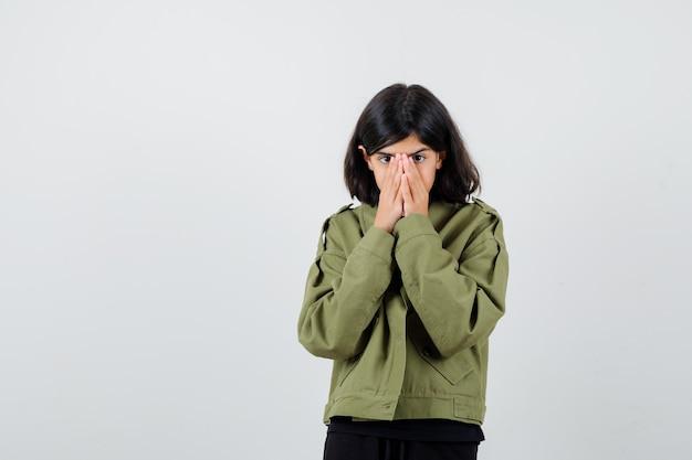 Teen dziewczyna trzymając się za ręce na ustach w koszulce, kurtce i patrząc przestraszony. przedni widok.