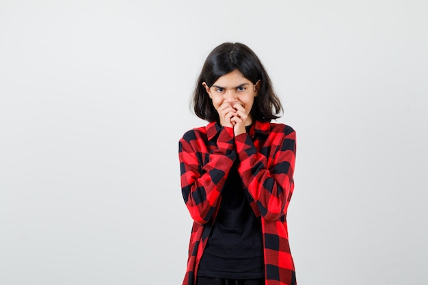Teen dziewczyna trzymając się za ręce na ustach w t-shirt, koszulę w kratkę i patrząc popiół, widok z przodu.