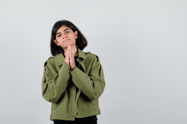 Teen dziewczyna trzymając się za ręce w geście modlitwy w t-shirt, zieloną kurtkę i patrząc z nadzieją. przedni widok.