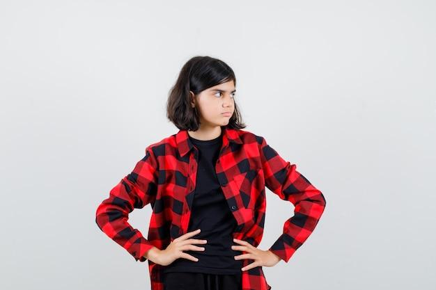 Teen dziewczyna trzymając się za ręce w talii, patrząc na bok w koszuli casual i patrząc niezdecydowany, widok z przodu.