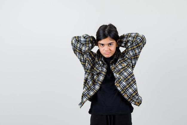Teen dziewczyna układając włosy w casual shirt i patrząc zamyślony, widok z przodu.