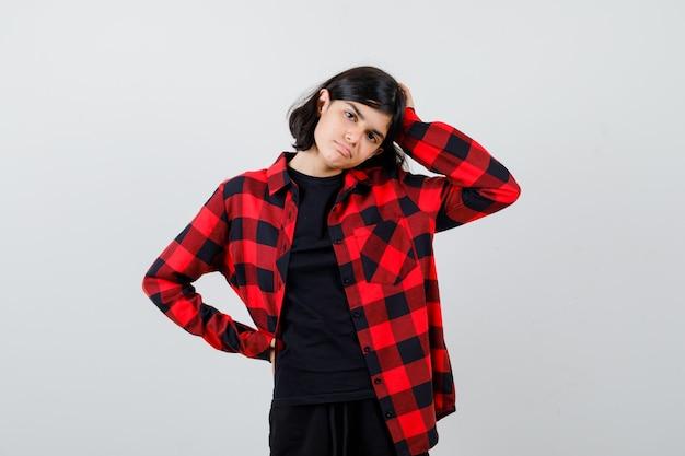 Teen dziewczyna w koszuli dorywczo trzymając rękę na głowie, trzymając rękę w pasie i patrząc niezdecydowany, widok z przodu.