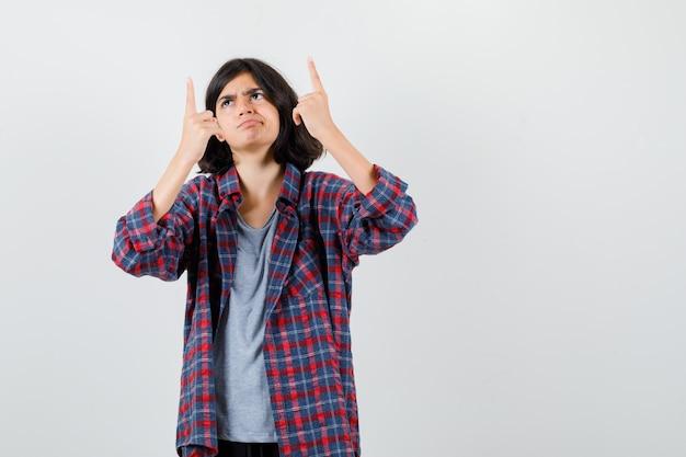 Teen dziewczyna w kraciastej koszuli, wskazując palcami i patrząc niezadowolony, widok z przodu.