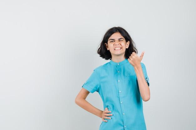 Teen dziewczyna w niebieskiej koszuli pokazuje kciuk do góry, mrugając i patrząc optymistycznie