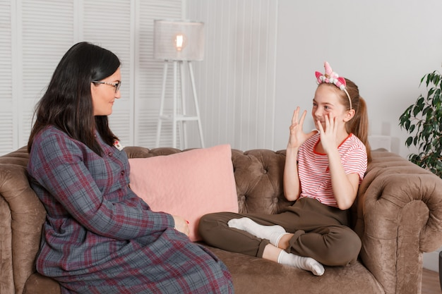 Teen dziewczyna w recepcji u psychoterapeuty. sesja psychoterapii dla dzieci. psycholog współpracuje z pacjentem. dziewczyny uśmiechnięty obsiadanie na kanapie obok siedzącej kobiety lekarki terapeuta