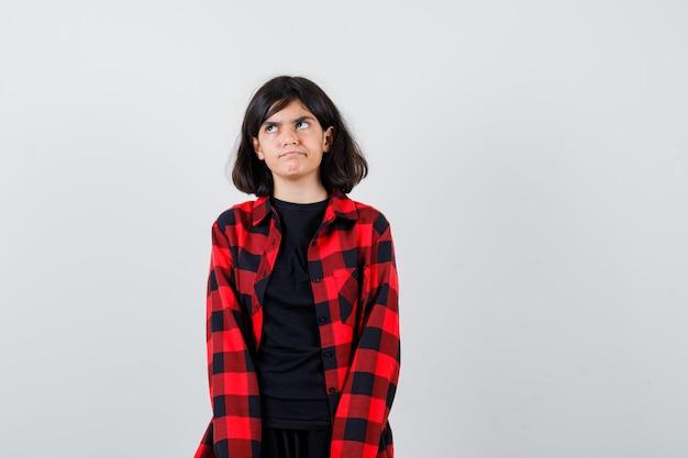 Teen Dziewczyna W T-shirt, Koszula W Kratkę Patrząc W Górę I Patrząc Zamyślony, Widok Z Przodu. Premium Zdjęcia