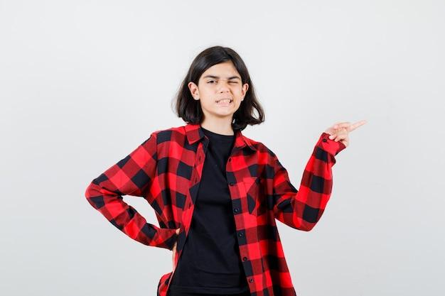 Teen dziewczyna w t-shirt, koszula w kratkę, wskazując na prawą stronę i patrząc zadowolony, widok z przodu.