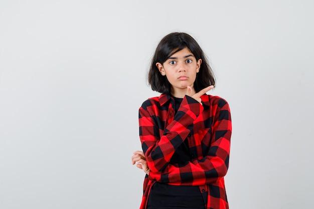 Teen dziewczyna w t-shirt, koszula w kratkę, wskazując w prawym górnym rogu i patrząc zakłopotany, widok z przodu.