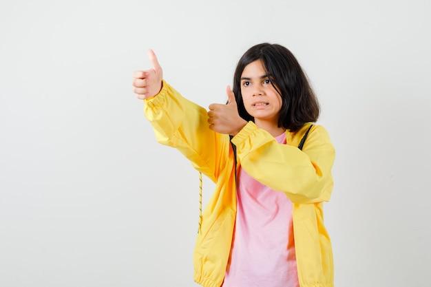 Teen dziewczyna w t-shirt, kurtka pokazując kciuk do góry i patrząc zadowolony, widok z przodu.