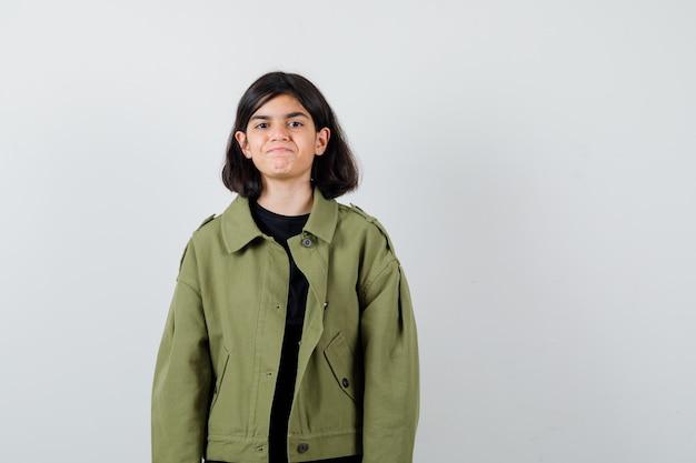 Teen dziewczyna w t-shirt, zielona kurtka i patrząc radosny, widok z przodu.
