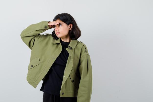 Teen dziewczyna w t-shirt, zielona kurtka, patrząc daleko z ręką nad głową i patrząc skupiony, widok z przodu.