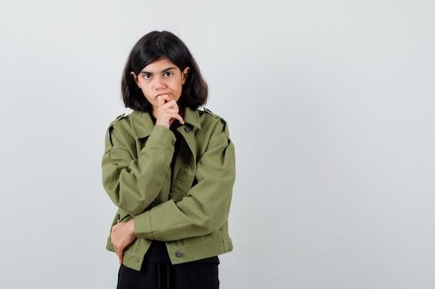 Teen dziewczyna w t-shirt, zielona kurtka podpierając podbródek pod ręką i patrząc ostrożnie, widok z przodu.