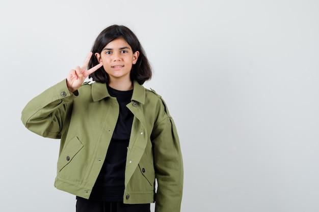 Teen dziewczyna w t-shirt, zielona kurtka pokazując znak zwycięstwa i patrząc wesoły, widok z przodu.