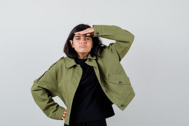 Teen dziewczyna w t-shirt, zielona kurtka trzymając rękę nad głową i patrząc pewnie, widok z przodu.