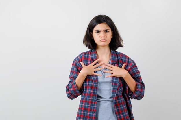 Teen dziewczyna w ubranie trzymając się za ręce na klatce piersiowej i patrząc ponury, widok z przodu.