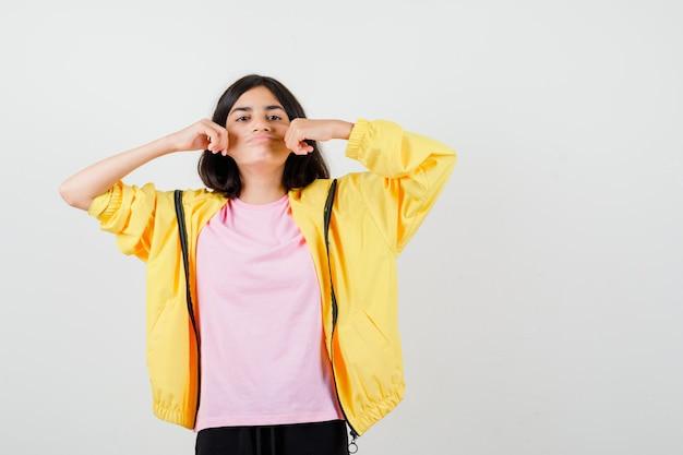 Teen dziewczyna w żółtym dresie, t-shirt, ciągnąc policzki na boki i patrząc tęsknie, widok z przodu.