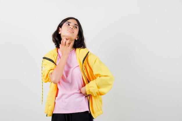 Teen dziewczyna w żółtym dresie, t-shirt, drapanie się po szyi ręką i patrząc w szoku, widok z przodu.