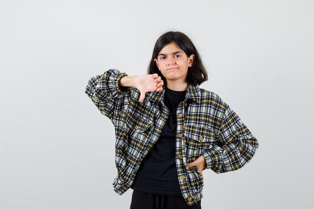 Teen dziewczyna wskazując kciukiem w dół, trzymając rękę w pasie w casualowej koszuli i patrząc zdenerwowany. przedni widok.