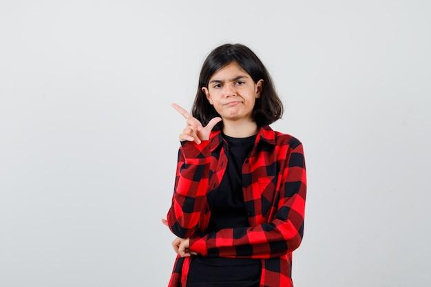 Teen dziewczyna wskazując na lewy górny róg w t-shirt, kraciaste koszule i niezadowolony. przedni widok.