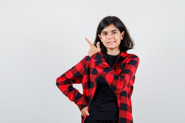 Teen dziewczyna wskazując na lewy górny róg w t-shirt, kraciaste koszule i patrząc radosny, widok z przodu.