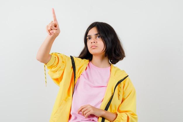 Teen dziewczyna wskazując palcem w żółty dres, t-shirt i patrząc tęsknie, widok z przodu.