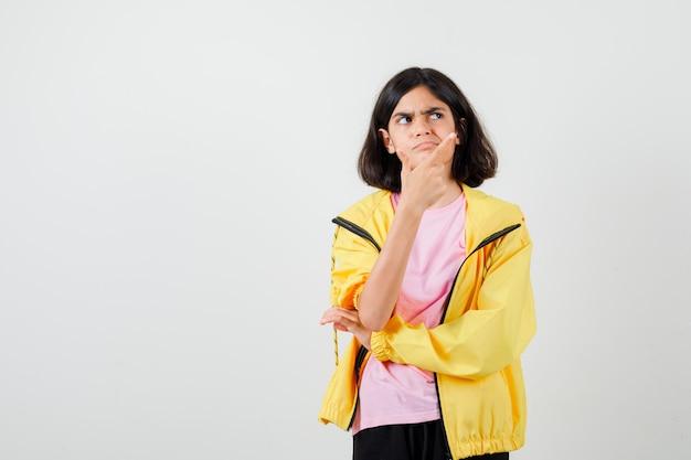 Teen dziewczyna wskazując w prawym górnym rogu, odwracając wzrok w t-shirt, kurtkę i patrząc zamyślony, widok z przodu.