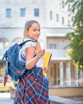Teen dziewczyna z plecakiem i folderem idzie do szkoły