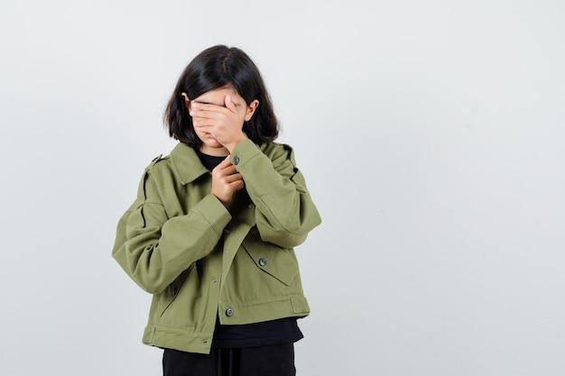 Teen dziewczyna zasłaniając oczy ręką w t-shirt, zieloną kurtkę i patrząc na zmęczoną. przedni widok.