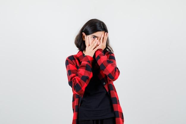Teen dziewczyna zasłaniając oko ręką, patrząc przez palce w koszulce, koszuli w kratkę i patrząc przestraszony, widok z przodu.