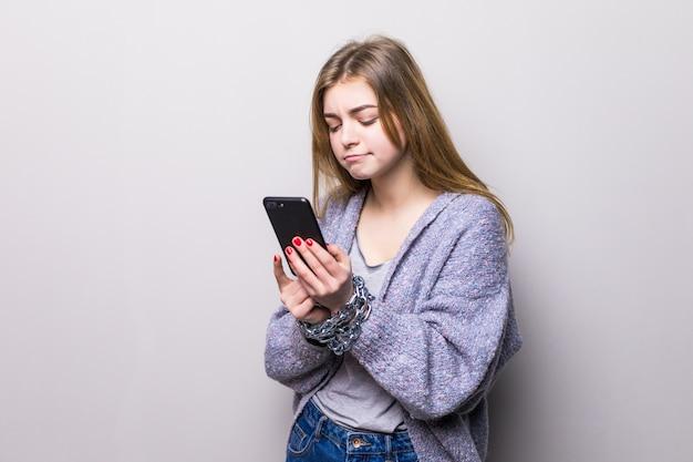 Teen girl z łańcuchem zablokowane ręce za pomocą smartfona na białym tle