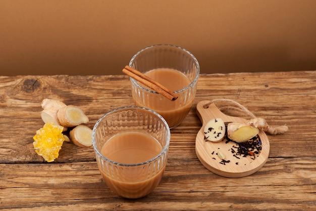 Teh tarik - herbata imbirowa w szklankach. kuchnia brunei, malezji i singapuru. warzony jest z mocno słodzonej czarnej herbaty z mlekiem lub skondensowanym mlekiem.