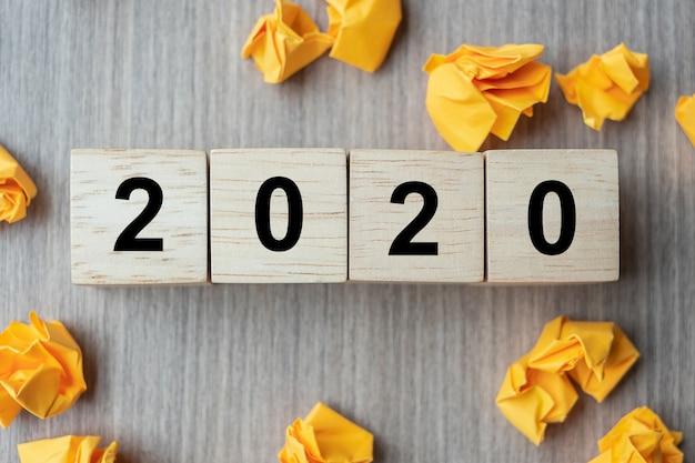 Tekst 2020 na drewnianych kostkach i pokruszonych papierach