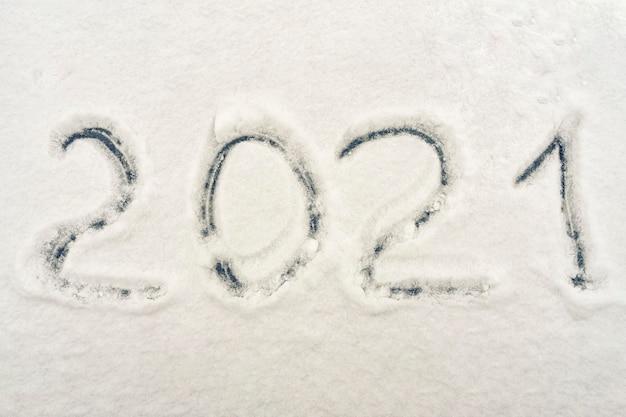 Tekst 2021 napisany na świeżym śniegu. symbol nowego roku