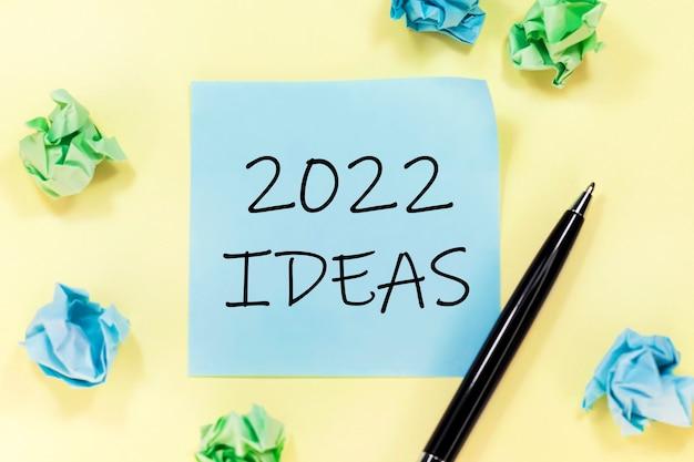 Tekst 2022 ideas na niebieskiej naklejce, czarny długopis i kartki na żółtym tle.