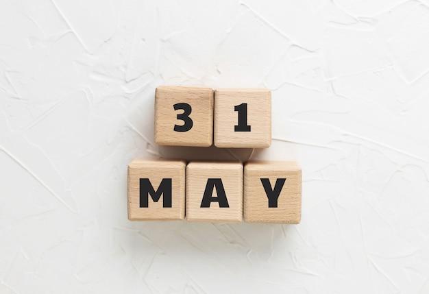 Tekst 31 maja wykonany z drewnianych kostek na białym, teksturowanym tle. memorial day 2021. amerykańskie święto. cześć i żałoba wojskowa. kwadratowe bloki drewniane. widok z góry, płaski układ.