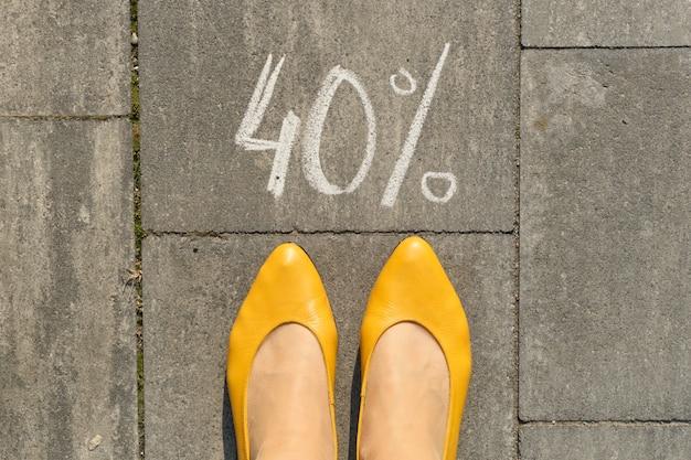 Tekst 40 procent napisany na szarym chodniku z nogami kobiety