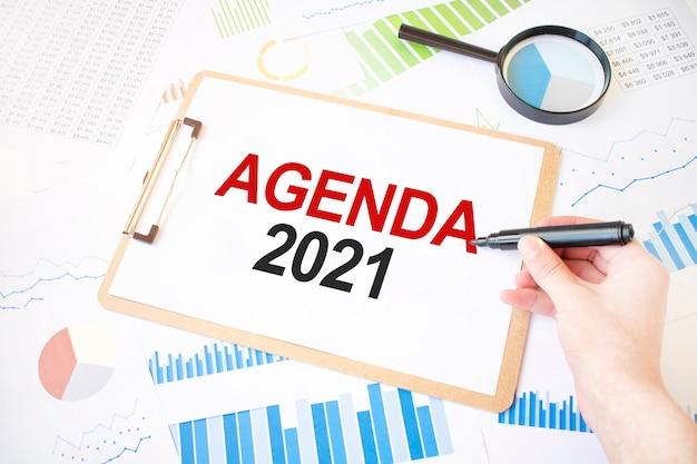 Tekst agenda 2021 na białej kartce papieru i znacznik na dłoni biznesmena na schemacie. pomysł na biznes