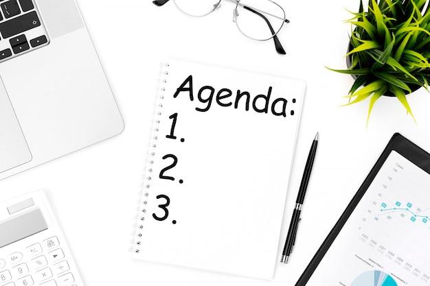 Tekst agenda w notatniku. laptop, kalkulator, schowek na wykres, okulary, długopis i roślinę. leżał z płaskim, koncepcja biznesowa.