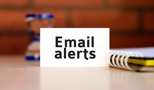 Tekst alertów e-mail na białej kartce z notatnikiem i klepsydrą