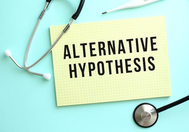 Tekst alternatywna hipoteza jest napisany w żółtym bloku, który leży obok stetoskopu na niebieskim tle.