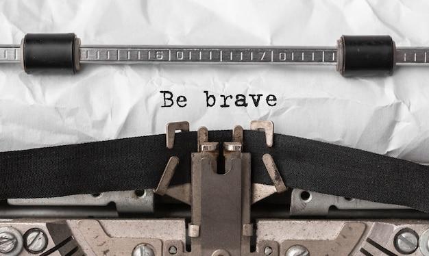 Tekst bądź odważny wpisany na maszynie do pisania retro
