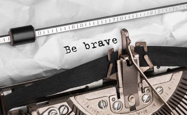 Tekst bądź odważny wpisany na maszynie do pisania w stylu retro