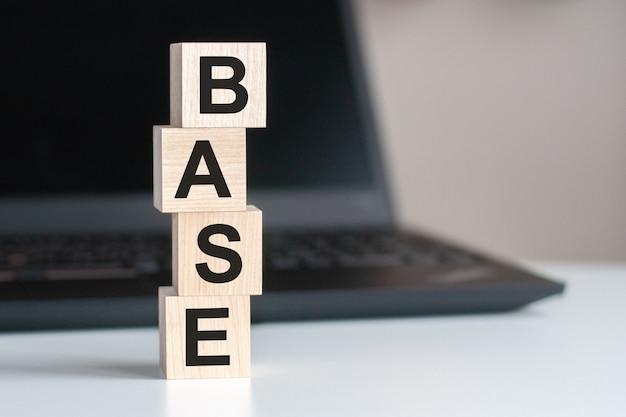 Tekst bazowy napisany na drewnianym bloku na klawiaturze komputera na czarnym tle. koncepcja wsparcia lub pomocy serwisowej.