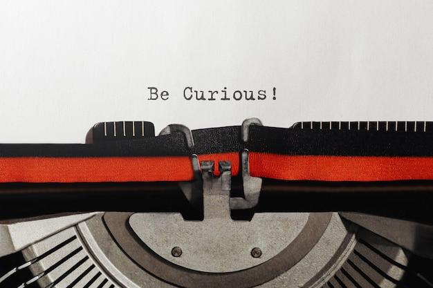 Tekst be curious wpisany na maszynie do pisania retro