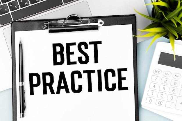Tekst best practice w schowku, długopisie, kalkulatorze, laptopie. pomysł na biznes.