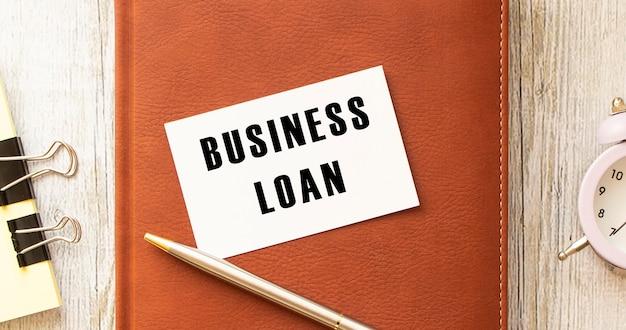 Tekst biznesowy pożyczka na białej karcie leżącej na notatniku na biurku. pomysł na biznes.