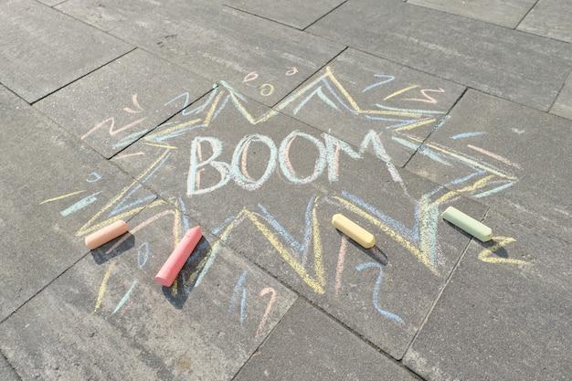 Tekst boom rysunek kredkami na szarym asfalcie