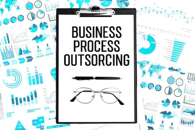 Tekst bpo business process outsourcing w schowku, długopisie, okularach, wykresach. leżał płasko.
