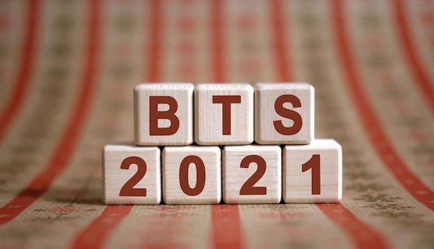 Tekst bts 2021 na drewnianych kostkach na monochromatycznym tle z odbiciem.